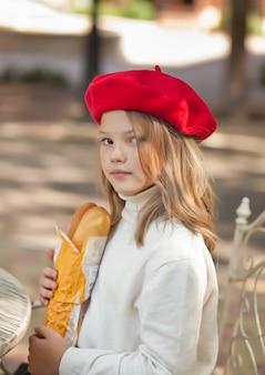 バゲットと屋外カフェに座っていると笑顔の赤い帽子のかわいい女の子。
