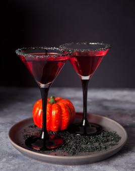 Два бокала с красным коктейлем для хэллоуина на темноте
