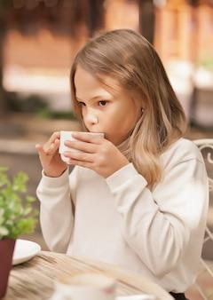 かわいい女の子笑顔と屋外カフェでカプチーノを飲む