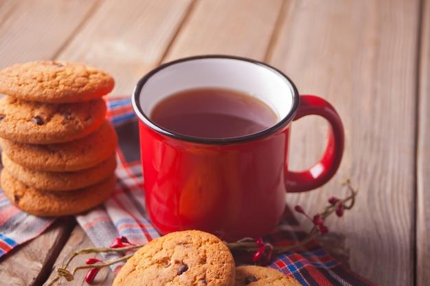 熱いお茶やコーヒー木製テーブルの赤いマグカップとクッキー