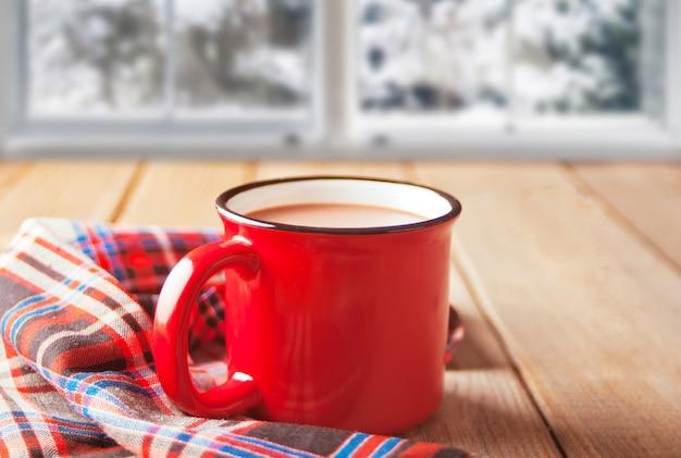 熱いお茶やコーヒーの木製のテーブルの赤いマグカップとクッキーの上の冷凍ウィンドウ。冬の暖かく居心地の良いコンセプト