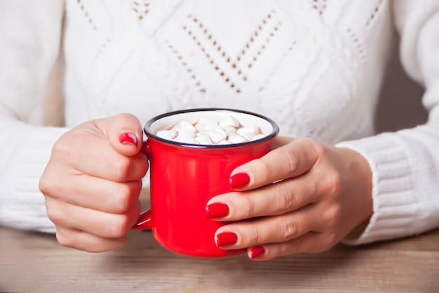 マシュマロとクリスマスココアの赤いマグカップを持っている女性の手。