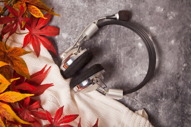 Уютная осень с музыкой для наушников и теплым вязаным пледом на сером. стиль жизни, осень, музыкальная концепция