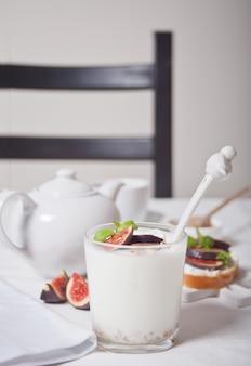 グラスにミューズリーとイチジクのフルーツを添えたヨーグルト、クリームチーズのサンドイッチ、イチジクと蜂蜜の白。健康食品 。