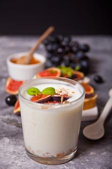 グラスにミューズリーとイチジクのフルーツを添えたヨーグルト、クリームチーズのサンドイッチ、イチジクと蜂蜜のコンクリート。健康食品 。秋の収穫。