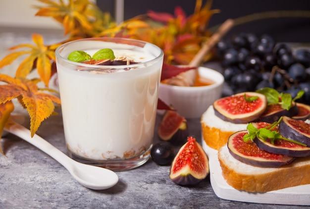 グラスにミューズリーとイチジクのフルーツを添えたヨーグルト、クリームチーズのサンドイッチ、イチジクと蜂蜜を小さな白いまな板の上で提供します。健康食品 。秋の収穫。