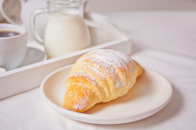 一杯のコーヒー、ミルクの瓶と白いプレートに新鮮なクロワッサンパン