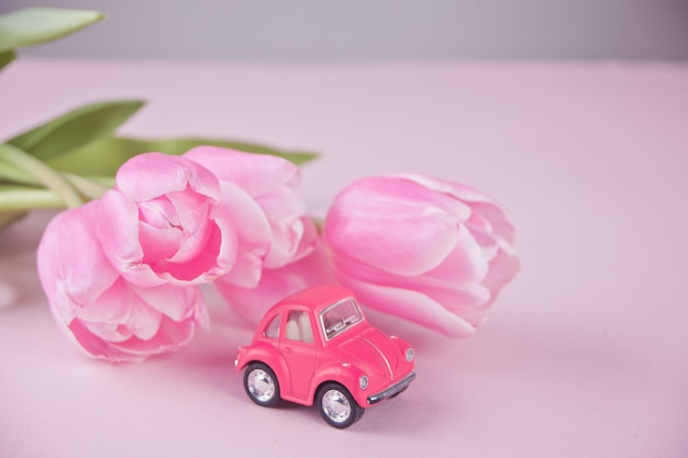 Маленькая игрушка розовая машина и розовые тюльпаны на розовом столе