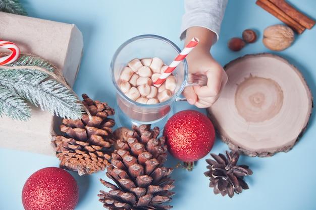 青いテーブルの上のマシュマロとクリスマスココアのガラスを持っている子供の手