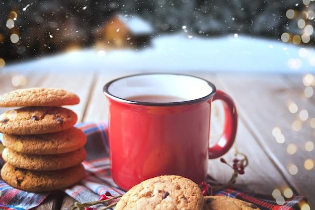 Печенье с красной кружкой горячего чая или кофе на деревянном столе с зимним пейзажем на заднем плане