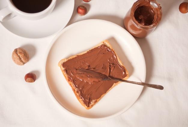 チョコレートクリームバター、白い背景の上のチョコレートクリームの瓶とパンのトースト。上面図。