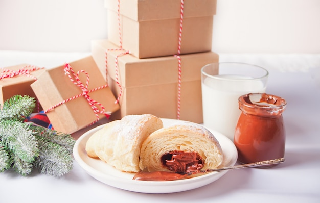 プレート、チョコレートミルク、ギフトボックス、白い背景の上の松の枝にチョコレートと焼きたてのクロワッサンパン