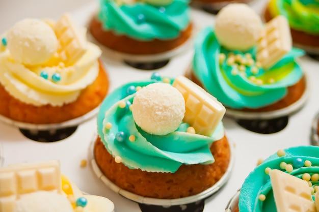 Закройте ванильные кексы с различными сливочным сыром и конфетами в бумажной коробке для подарка