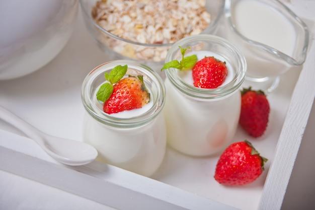 Натуральный домашний йогурт в стеклянной банке со свежей клубникой и мюсли поблизости