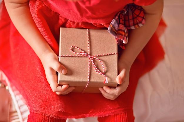 Ребенок девочка в красном платье, держа в руках рождественский подарок