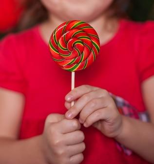 Милая маленькая девочка в красном платье держа карамельку леденца на палочке в руках.