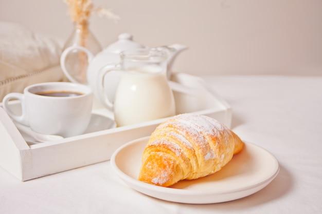 Свежая булочка с круассаном на белой тарелке с чашкой кофе, банку молока на деревянный поднос.