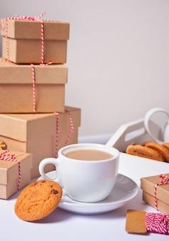 Чашка чая, домашнее печенье, рождественские подарочные коробки и рождественский декор на белом.