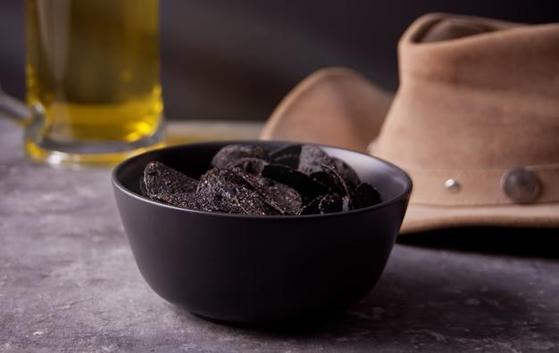 Мексиканские кукурузные чипсы начос, бокал пива и ковбойская шляпа. черные чипсы начос для брутальных мужчин.