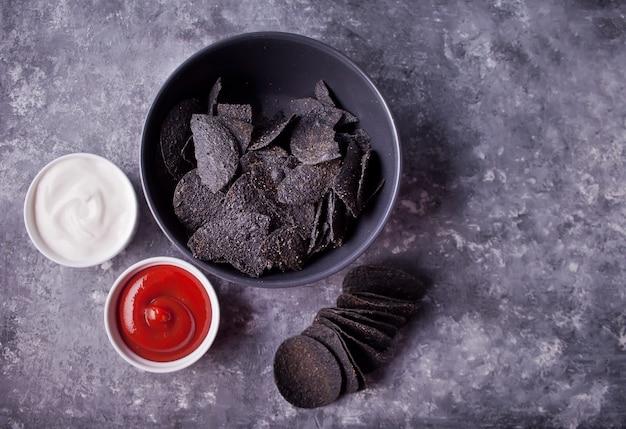 Мексиканские кукурузные чипсы начос с соусами. черные чипсы начос для брутальных мужчин. вид сверху.