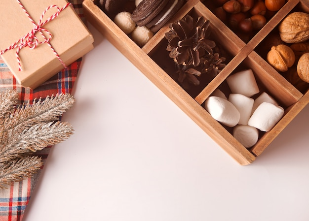 マシュマロ、クッキー、ナッツ、松の枝が付いているギフトボックス近くのクリスマス木製ボックス