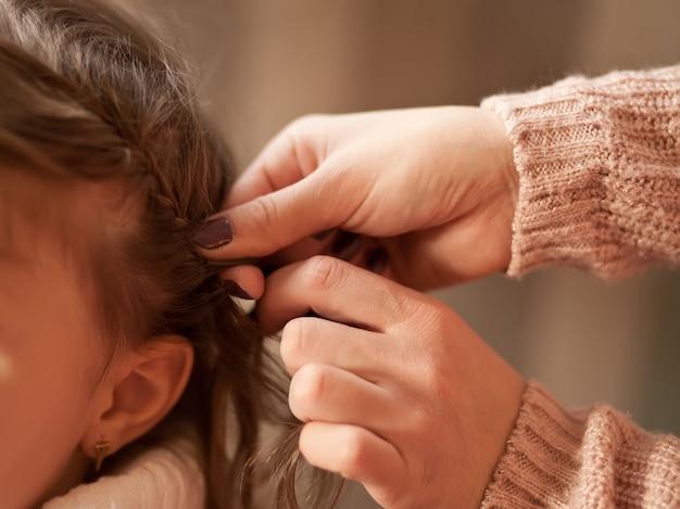 母は彼女のブルネットの小さな娘のおさげ髪を編んだ。