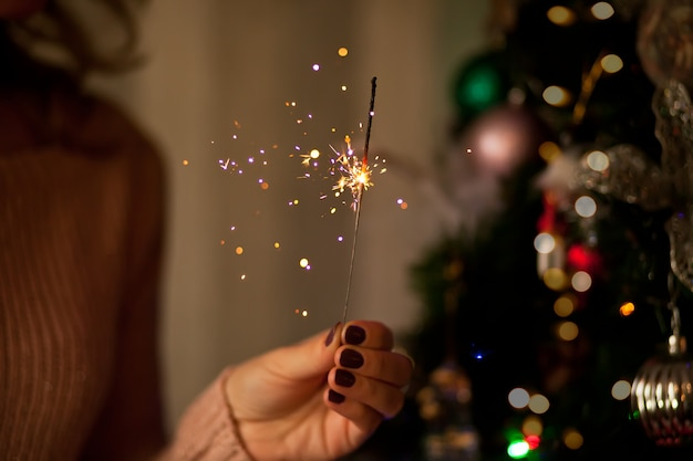 暗いお祭り部屋できれいな女性の手で輝く線香花火。メリークリスマス、そしてハッピーニューイヤー。