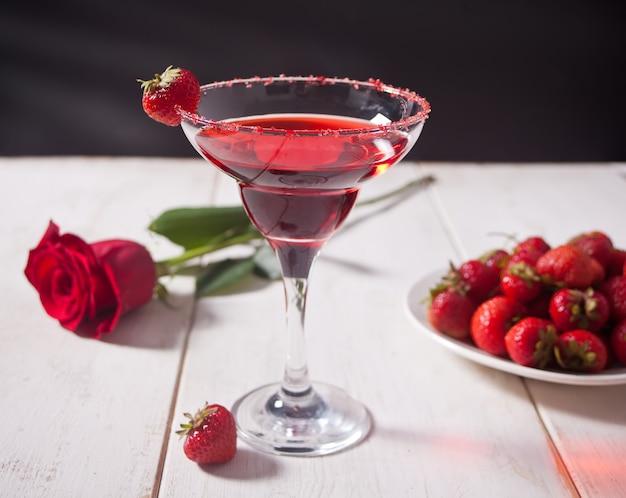 透明なガラスの赤いエキゾチックなアルコールカクテル、新鮮なイチゴとロマンチックなディナーの木製の白いテーブルに赤いバラのプレート。