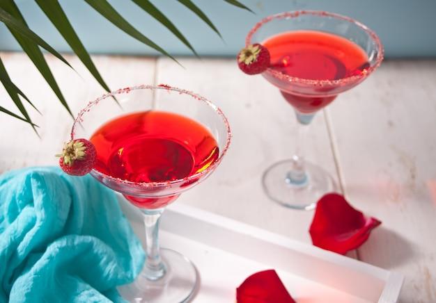 ロマンティックなディナーには、透明なグラスと木製の白いテーブルに赤いバラの花びらの赤いエキゾチックなアルコールカクテル。