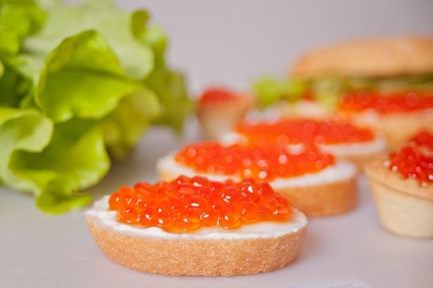 Свежая красная икра на хлеб. бутерброды с красной икрой. деликатесы. изысканная еда