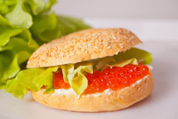 Свежая красная икра на бублик хлеба. бутерброд с красной икрой. гастроном. изысканная еда
