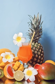 プルメリアの花と背景に果物と熱帯のエキゾチックなマルチフルーツジュースカクテルのグラス