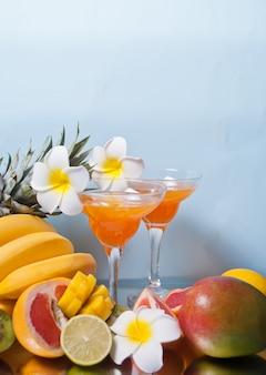 熱帯のエキゾチックなマルチフルーツジュースカクテルのグラスは、フランジパニの花と背景にフルーツと飲む