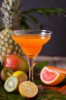 トロピカルなエキゾチックなマルチフルーツジュースカクテルドリンクグラスと近くの果物