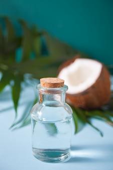 ココナッツ、プルメリアプルメリアの花、緑のヤシの木の葉のボトルにココナッツオイル。健康食品、スキンケアのコンセプト。