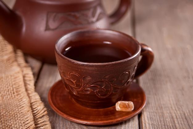 Чашка чая и сахара с чайником на фоне
