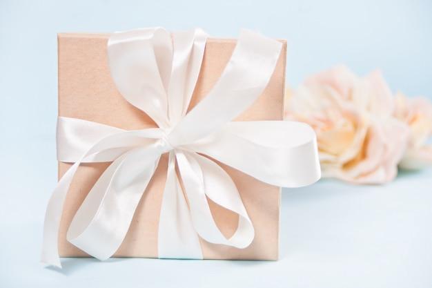 Подарочная коробка с цветами бежевых роз на фоне.