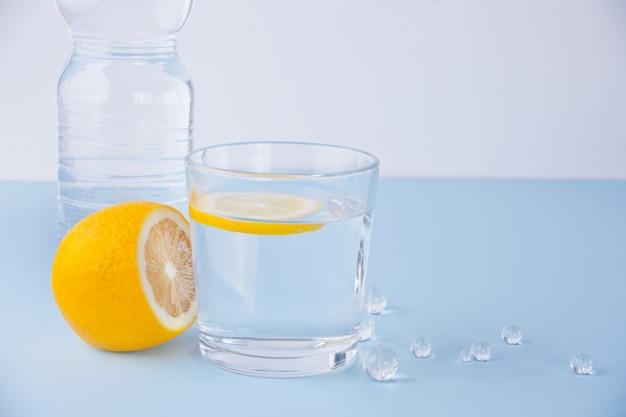 青いテーブルの上の水のガラス、ボトル、レモンフルーツ。