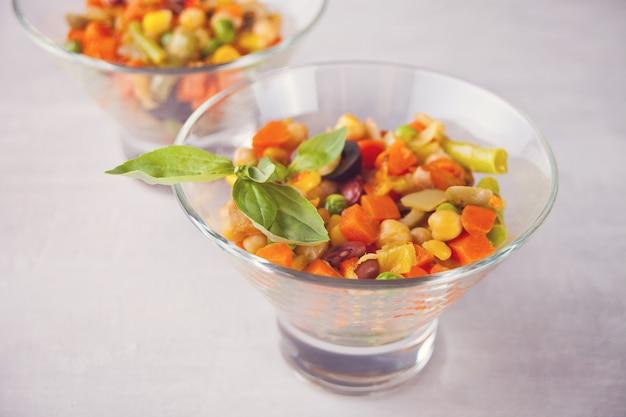 Домашний мексиканский салат в мисках с фасолью, кукурузой, помидорами, перцем и другими овощами.