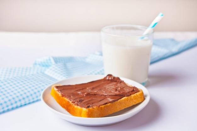 Хлеб тост с шоколадно-сливочным маслом, стакан молока на белой поверхности