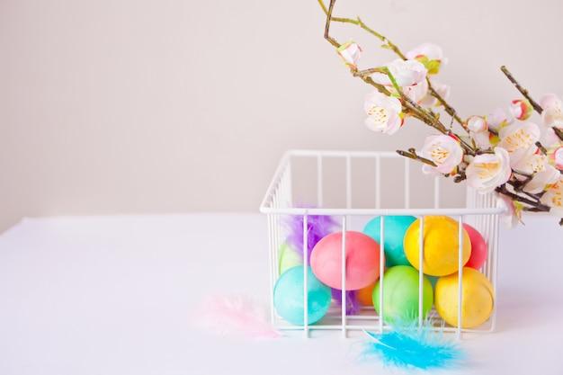 バスケットと桜の枝でイースターの日のためのカラフルな卵。コピースペース。