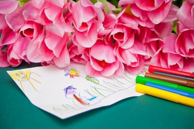 ピンクのチューリップと子供の絵。母の日、誕生日、イースターの日に母への贈り物。