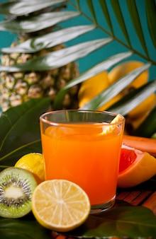 パイナップル、果物、ヤシの葉と熱帯のエキゾチックなマルチフルーツジュースのガラス