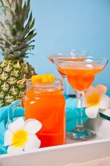 果物と木製の白いトレイに熱帯のエキゾチックなマルチフルーツジュースのグラス。