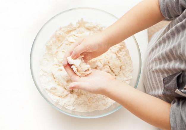 ピザや別の食品の生地を準備する家庭の台所で小さな子供。上面図。