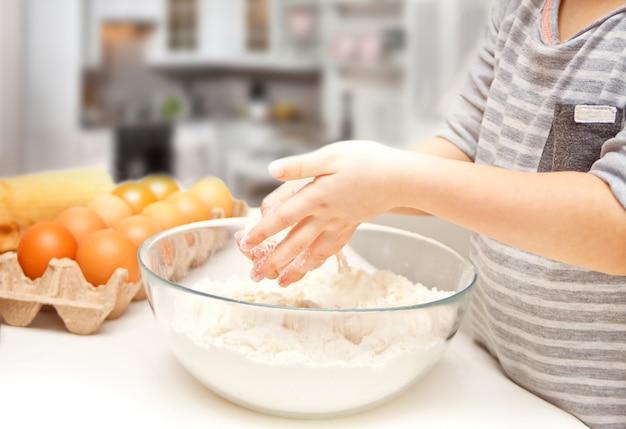 ピザや別の食品の生地を準備する家庭の台所で小さな子供。