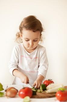 Милая кудрявая девушка готовит овощи для салата в домашней кухне. здоровое питание.