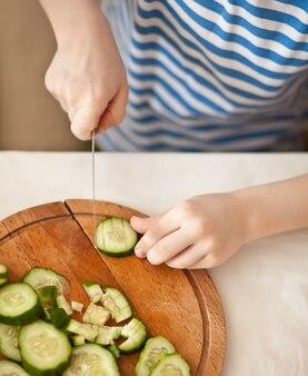 Малыш мальчик готовит овощи для салата в домашней кухне. здоровое питание.