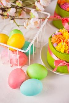 春のイースターお祝いテーブル。表面にバタークリームの花と色とりどりの卵が入った小さなグリーンケーキ。