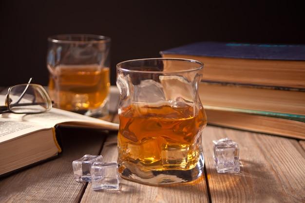 Виски со льдом на деревянном столе. рядом старые книги.